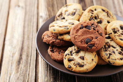 Chocolate chip cookies on a grey plate and wood background