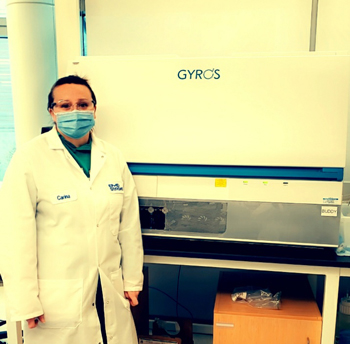 Carina Carter stands in front of the Gyrolab automated immunoassay platform